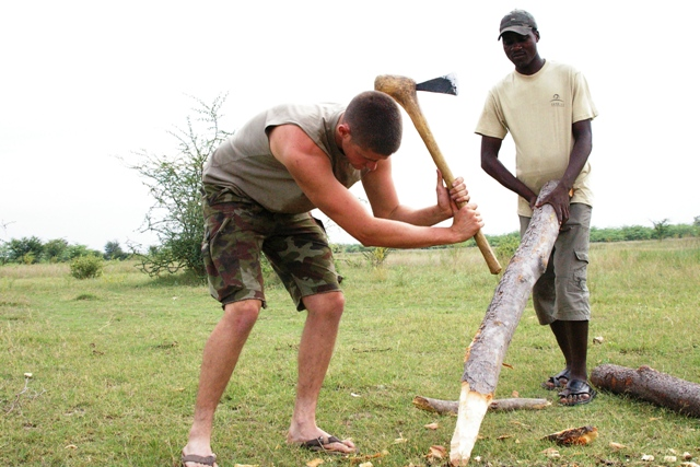 Volunteer using axe to cut poles